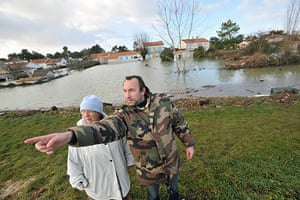 Storm damage in Europe: Two people look at damage caused by heavy floods  in La Faute-sur-Mer