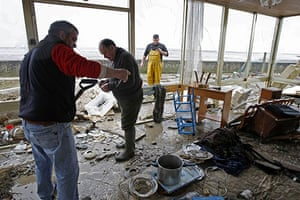 Storm damage in Europe: Men clear debris from a home in the village of Chatelaillon sur Mer
