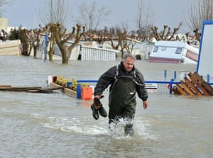 Storm damage in Europe: A man walks in a flooded camping site in La Faute-sur-Mer, western France