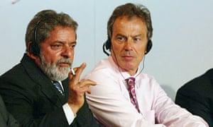 Brazilian President Luiz Inacio Lula Di Silva smokes at a symposium.