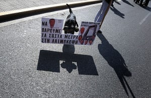 more strikes in greece: A dog carries a placard with an anti-capitalist message in Athens
