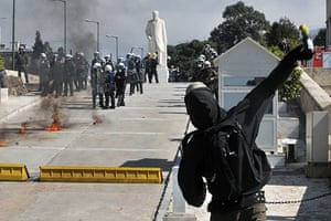 more strikes in greece: A protestor throws petrol bomb towards police