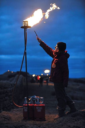 Hadrian's Wall: A volunteer lights her flame as torches are lit