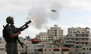 An Israeli border police officer fires tear gas towards Palestinian stone-throwers