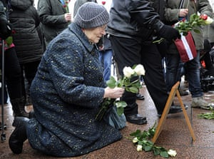 Legionnaires' Day Latvia: An elderly woman lays flowers at the Freedom Monument