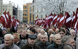 Legionnaires' Day Latvia: People march in a procession between Latvian flags