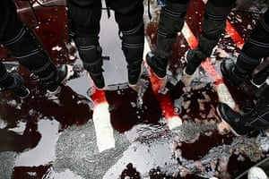 24 hours in pictures: Thai police stand reflected in a pool of blood during red shirt protest