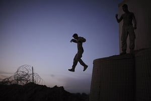 24 hours in pictures: A US Marine jumps from an observation point Marjah, Afghanistan