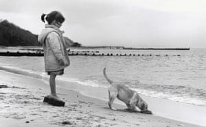 Tall tails: Girl and dog on beach