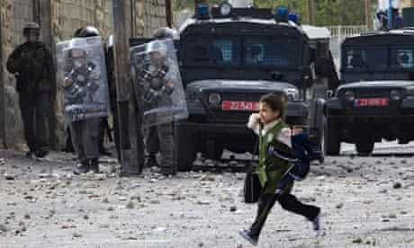 A girl runs past Israeli troops  during clashes with Palestinians in East Jerusalem yesterday