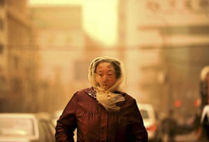 Sandstorms in China: a woman walks in the dust brought by standstorm in Lanzhou