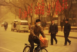 Sandstorms in China: A man cycles during a sandstorm in Beijing