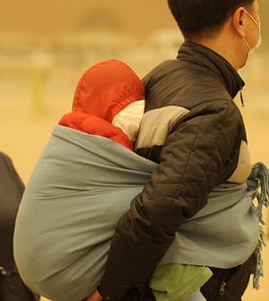 Sandstorms in China: A man carries a baby wrapped up against a sandstorm in Beijing