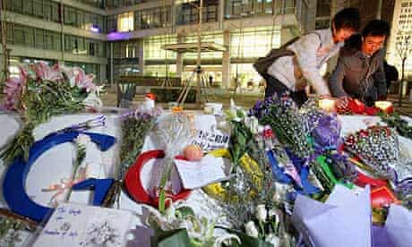 Visitors to Google's Beijing headquarters in China light candles and place flowers on a company logo