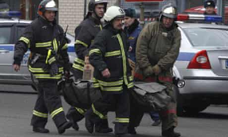 Firefighters carry a body from Lubyanka metro station to an ambulance in Moscow