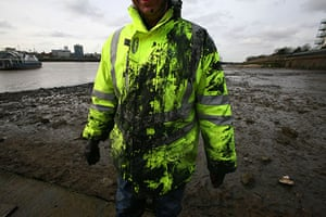 Cleaning the Thames: A volunteer covered in mud
