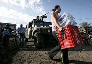 Chile Aid: Woman carries water bottles to be handed out to earthquake victims, Chile