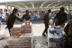 Chile Aid: Chilean soldiers separate donated food into packages for distribution