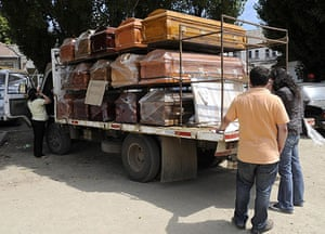 Chile Aid: Municpal employees check coffins next to a hospital in Constitucion, Chile