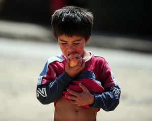 Chile Aid: A child eats an apple after food was distributed in Constitucion, Chile