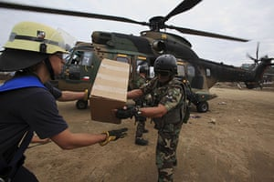 Chile Aid: Troops and firefighters unload aid from military helicopter, Dichato, Chile
