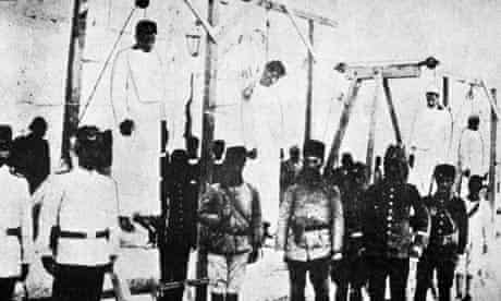 Ottoman soldiers pose with hanged Armenians