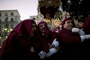 Holy week: A foreman helps a penitent as he carries the statue in Malaga