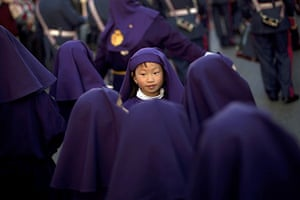 Holy week: Malaga, Spain: A young penitent takes part in the procession