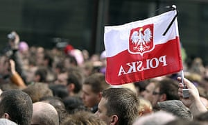 A mourner waves a Polish flag in front of the presidential palace in Warsaw