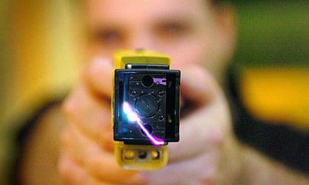 A police officer demonstrating a Taser gun