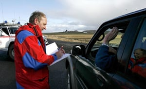 Iceland volcano eruption: An emergency worker records a driver's details
