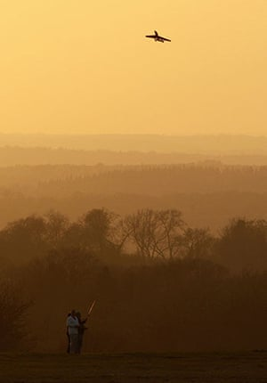 Volcanic sunsets: A man flies his model aeroplane during a sunset at Epsom Down