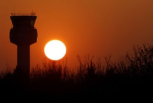 Volcanic sunsets: The sun sets behind the air traffic control tower at East Midlands airport