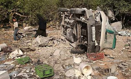Palestinians walk past what Hamas officials say is factory destroyed in Israeli air strike