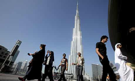 A group of Emiratis walk past the Burj Dubai Tower, the tallest tower in the world