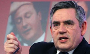 Gordon Brown speaks in front of an image of Tory leader David Cameron
