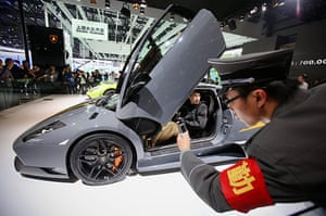 Beijing car show: Chinese security personnel takes pictures beside a Lamborghini Murciélago
