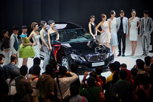 Beijing car show: Models stand beside the world premiere display of Mercedes-Benz E300 L car