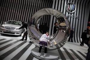 Beijing car show: A child rests on a sculpture at the Buick booth