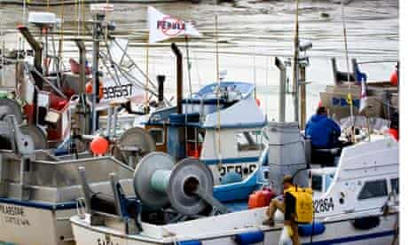 Fishing boats with an anti-pebble mine flag