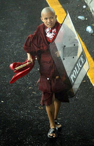Thailand protests: A monk carrying a riot police shield joins anti government protesters