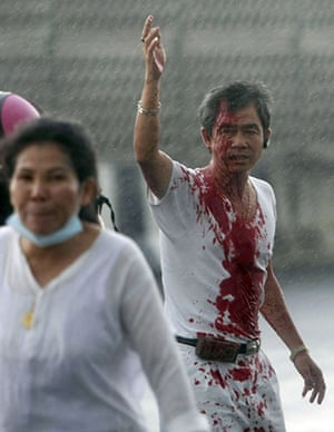 Thailand protests: An injured protester waves for help