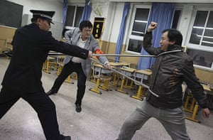 China school violence: Police officers demonstrate with a teacher the use of defensive steel forks