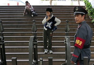 China school violence: A security guard stands at the entrance of a school in Nanjing,