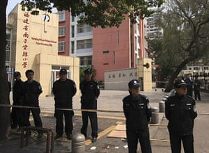 China school violence:  Policemen guard the entrance of a primary school in Nanping