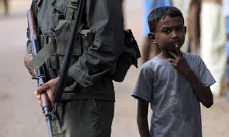 A Tamil refugee stands beside a soldier at an internment camp in October 2009