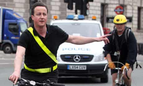 Conservative party leader David Cameron arrives by bicycle at the House of Commons in central London