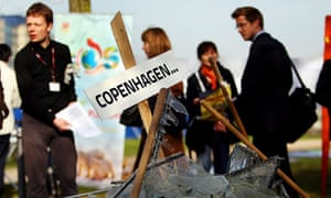 Delegates of the UN climate change talks pass a symbolic pile of broken glass in Bonn, Germany