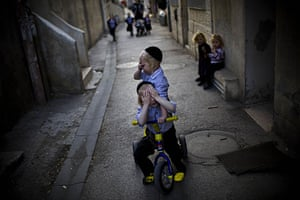 24 hours in pictures: Jerusalem:  Jewish children cover their faces as they play in a street