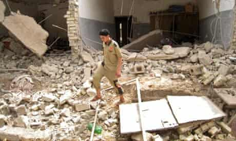 An Iraqi man walks through rubble at the site of a bombing that targeted police in Fallujah, Iraq.